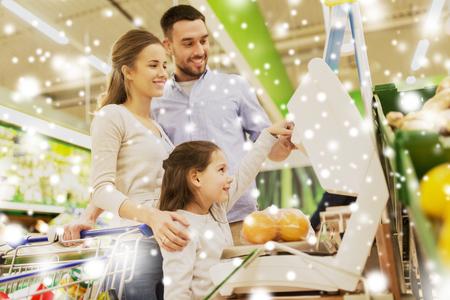 La famille de pesée des oranges à l'échelle à l'épicerie Banque d'images - 88527140