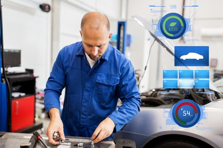 mechanic man with wrench repairing car at workshop Stock Photo