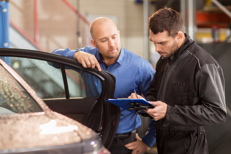 auto mechanic and customer at car shop 版權商用圖片