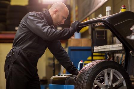 auto mechanic balancing car wheel at workshop