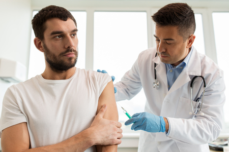 patient and doctor with syringe doing vaccination Stockfoto