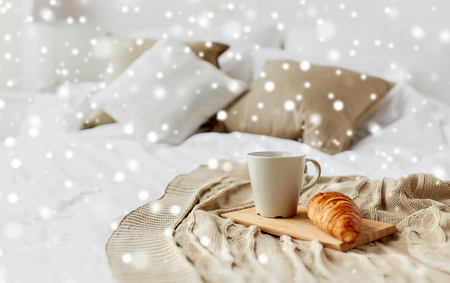 coffee cup and croissant on plaid in bed at home Stock Photo