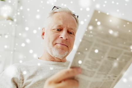 Sluit omhoog van de hogere krant van de mensenlezing thuis Stockfoto