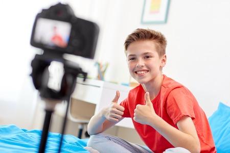 Gelukkige jongen met camera opnemen video thuis