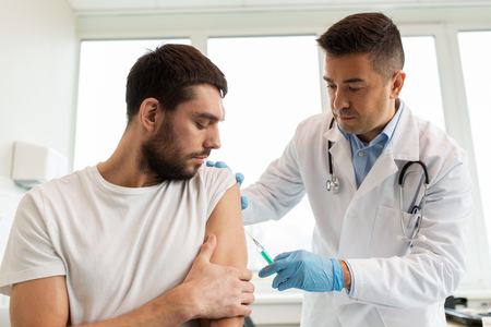 patient and doctor with syringe doing vaccination Stock Photo
