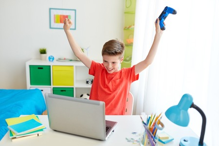 boy with gamepad playing video game on laptop Stock Photo