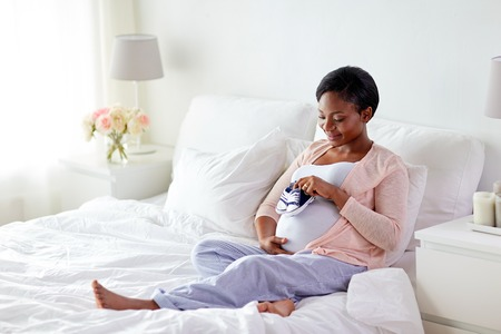 pregnant african woman with baby bootees in bed