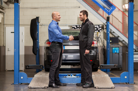 mechanic and customer shaking hands at car service
