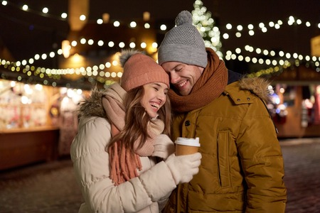 クリスマス マーケットでコーヒーを飲みながら幸せな若いカップル