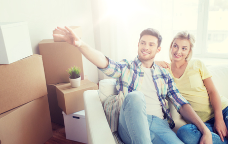 people, repair and real estate concept - smiling couple with boxes moving to new home and dreaming Stock fotó