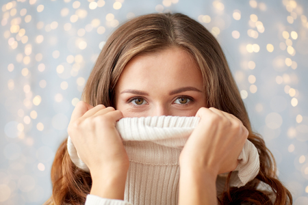 young woman or teen girl pulling pullover collar