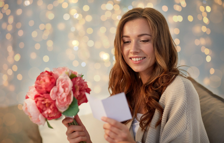 happy woman with flowers and greeting card at home Фото со стока