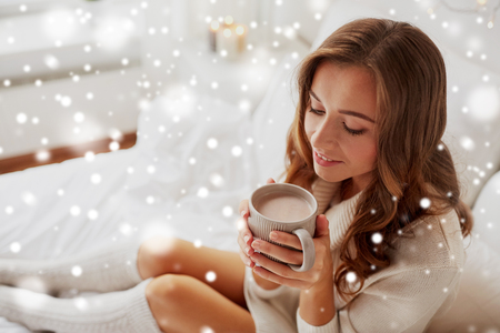 close up of happy woman with cup of cocoa at home