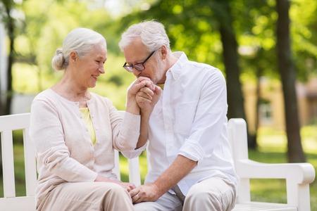 公園でベンチに座って幸せな先輩カップル 写真素材