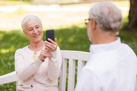 old woman photographing man by smartphone in park Stock Photo