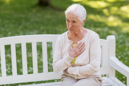 Senior vrouw ziek voelen in zomer park Stockfoto