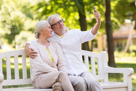 senior couple taking selfie by smartphone at park Stock Photo