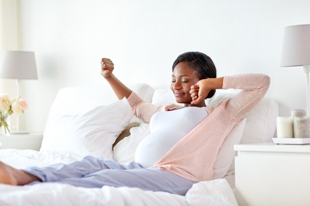 happy pregnant african woman stretching in bed