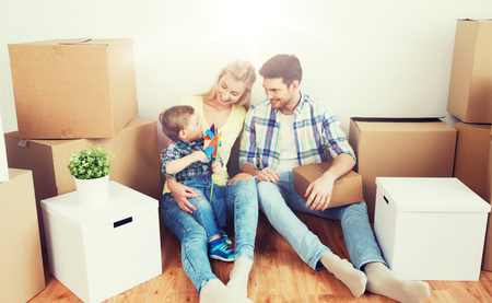 famille heureuse avec des boîtes à côté de la nouvelle maison