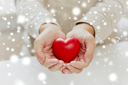 close up of senior man with red heart in hands