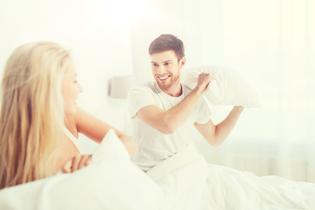 happy couple having pillow fight in bed at home Stock Photo