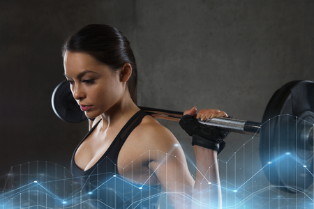 young woman flexing muscles with barbell in gym Stock Photo
