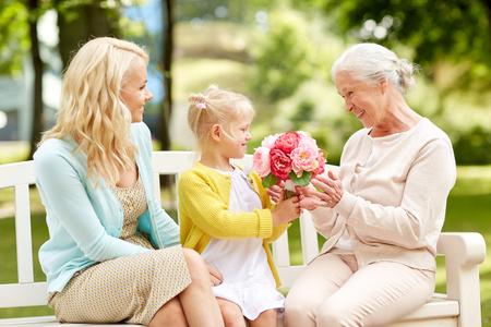 Familia feliz dando flores a la abuela en el parque Foto de archivo - 89211710