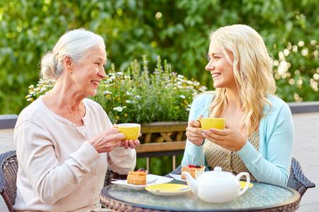 fille avec une mère âgée, boire du thé au café