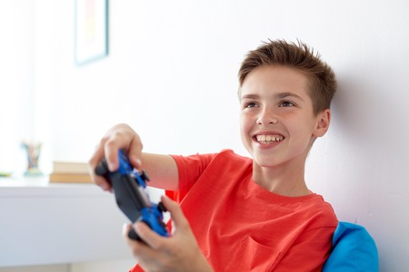 happy boy with gamepad playing video game at home 版權商用圖片