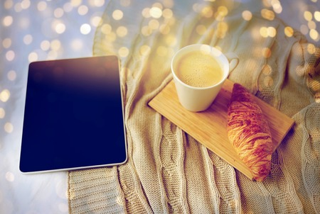 tablet pc, coffee and croissant on bed at home Stock Photo