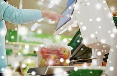 Femme pesant des pommes sur une balance à l'épicerie Banque d'images - 89289946