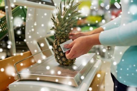 Client avec ananas à l'échelle à l'épicerie Banque d'images - 89290701