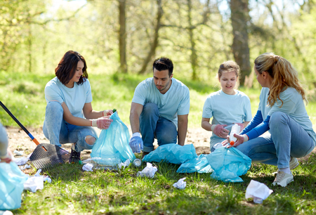 selfless: volunteers with garbage bags cleaning park area