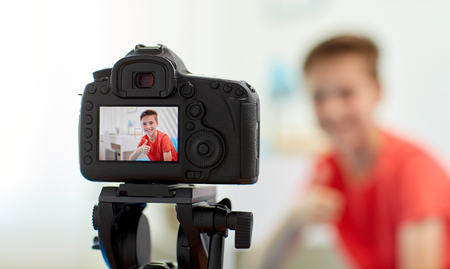 camera recording video of blogger boy at home Stock Photo