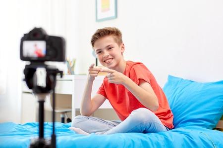 Gelukkige jongen met camera opnemen video thuis Stockfoto