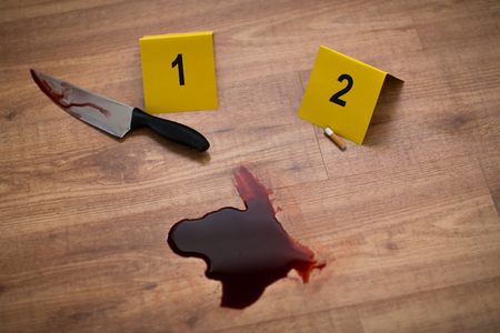 knife in blood and evidence marker at crime scene