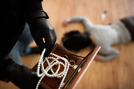 criminal with knife and jewelry at crime scene Stock Photo - 89431076
