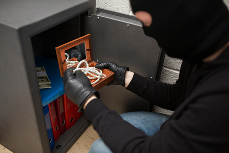 thief stealing valuables from safe at crime scene