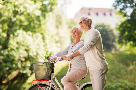 happy senior couple with bicycle at summer park Reklamní fotografie