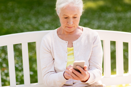 senior woman with smartphone at summer park