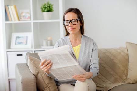 vrouw in glazen thuis krant lezen Stockfoto