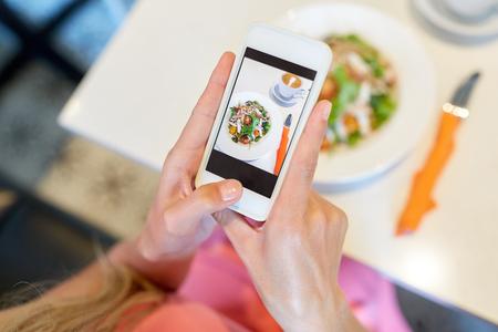 カフェでスマートフォン撮影食品を持つ女性