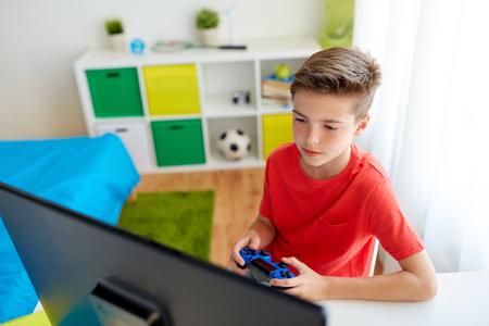 Ragazzo con gamepad che gioca video gioco sul computer Archivio Fotografico
