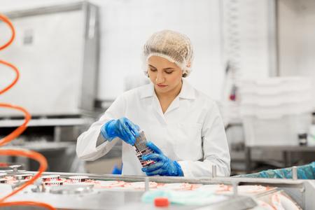 mujer que trabaja en el transportador de la fábrica de helados