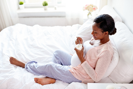 pregnant woman eating yogurt in bed Stock Photo