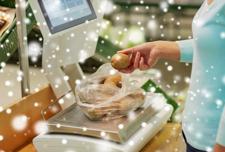 Client avec des pommes de terre à l'échelle à l'épicerie Banque d'images - 89831480