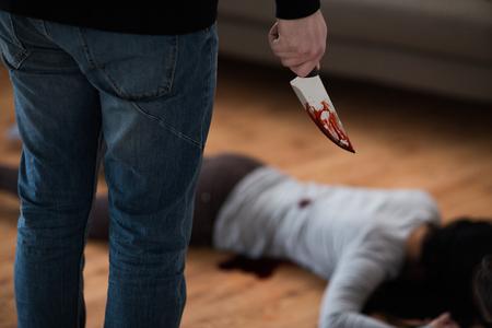 criminal with knife and dead body at crime scene Foto de archivo