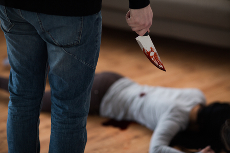 criminal with knife and dead body at crime scene Stockfoto