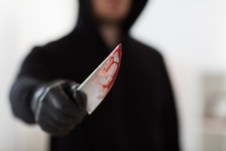 close up of criminal with blood on knife Stock Photo