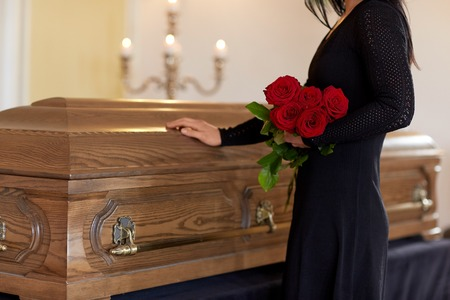 sad woman with red roses and coffin at funeral